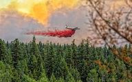 Lockheed L-188 drops fire retardant to suppress a massive firestorm in Canada title=